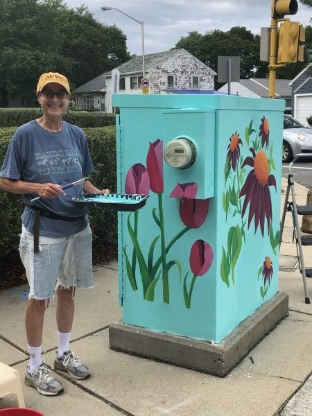 Anne painting her utility box at the corner of Brighton and Cross streets in Belmont. © Photo by Carl Katzeff.