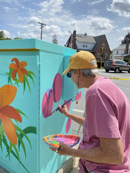 Anne painting in the first color on the tulips panel of the transformer box